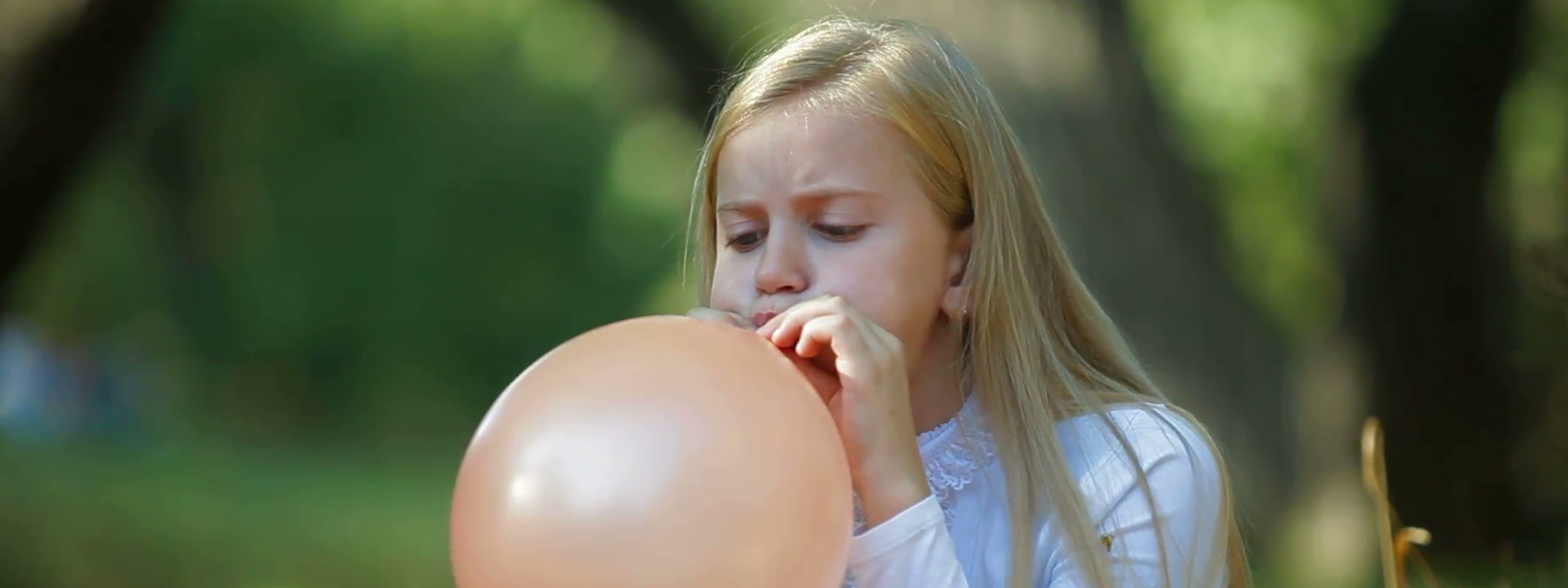 face-of-funny-little-girl-blowing-up-a-balloon-outdoors_vuejbcorol__F0000_.